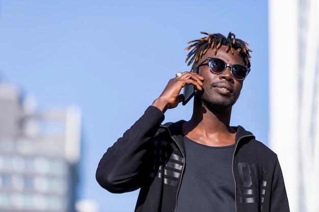 Vue de face de l'homme noir avec des lunettes de soleil debout contre le paysage urbain dans la rue tout en utilisant un téléphone portable en journée ensoleillée.