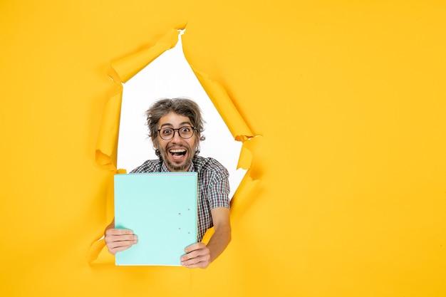 Vue de face d'un homme ordinaire avec un fichier sur un mur déchiré jaune