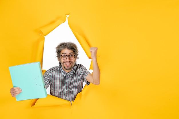 Vue de face d'un homme ordinaire avec un fichier sur un mur jaune