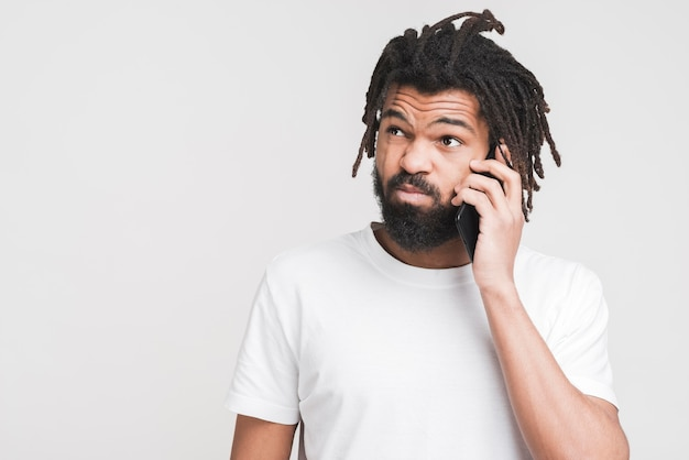 Vue de face homme parlant sur son smartphone