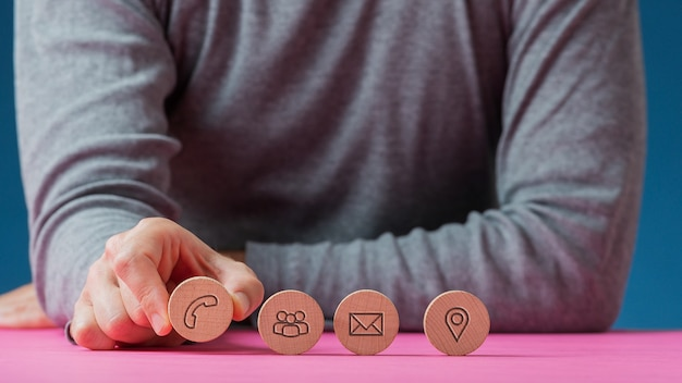 Vue de face d'un homme plaçant quatre cercles coupés en bois avec des icônes de contact et de communication sur eux dans une rangée sur un bureau rose.