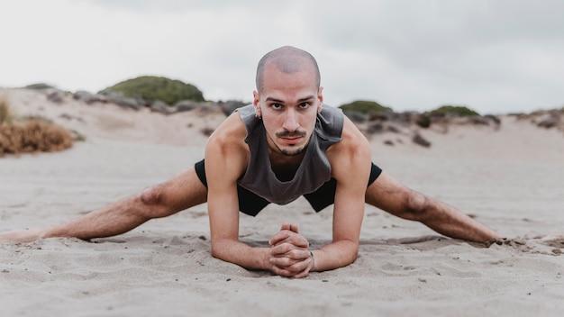 Vue de face de l'homme sur la plage, exerçant des positions de yoga sur le sable
