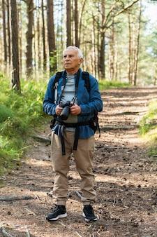 Vue de face d'un homme plus âgé voyageant avec sac à dos et appareil photo dans la nature
