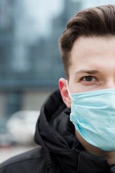Vue de face d'un homme portant un masque médical dans la ville
