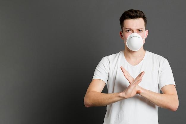 Vue de face d'un homme portant un masque médical et faisant un x avec ses mains