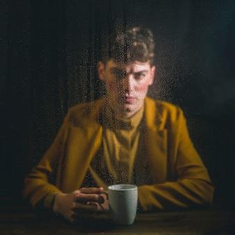 Vue de face homme posant avec une tasse