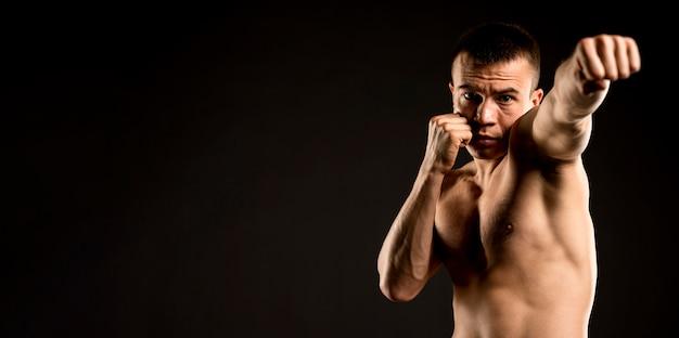 Vue de face de l'homme pratiquant la boxe avec copie espace
