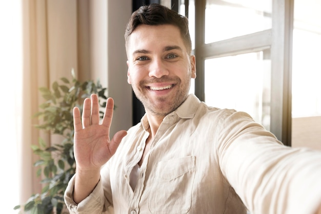 Vue de face homme prenant selfie avec la main vers le haut