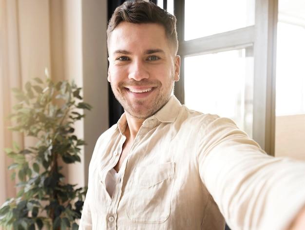 Vue de face homme prenant selfie