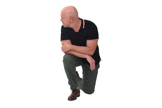 Vue de face d'un homme regardant loin s'appuyant sur un genou au sol sur fond blanc