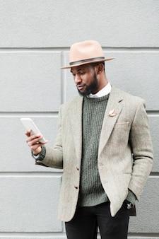 Vue de face homme regardant son téléphone à l'extérieur