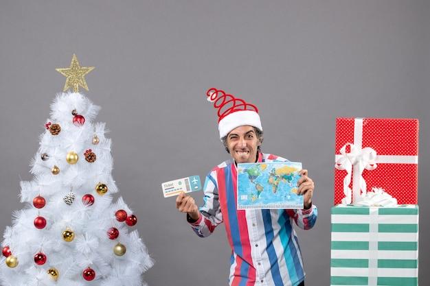 Vue de face homme riant tenant carte du monde et billet de voyage près de l'arbre de noël blanc