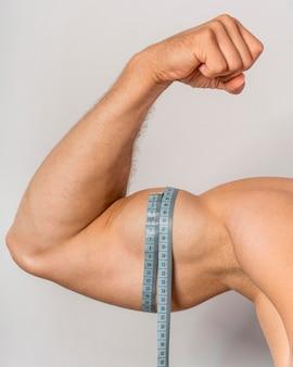 Vue de face de l'homme avec un ruban à mesurer sur les biceps