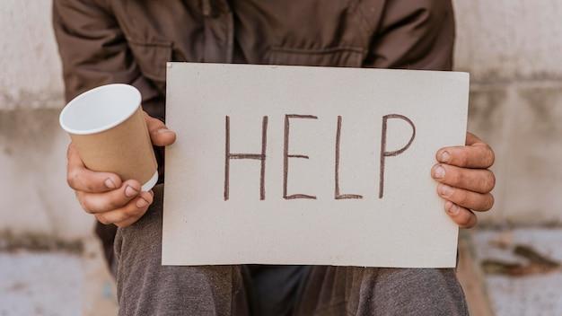 Vue de face de l'homme sans-abri tenant signe d'aide et tasse