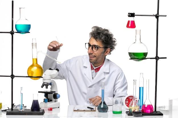 Vue de face de l'homme scientifique travaillant avec des solutions