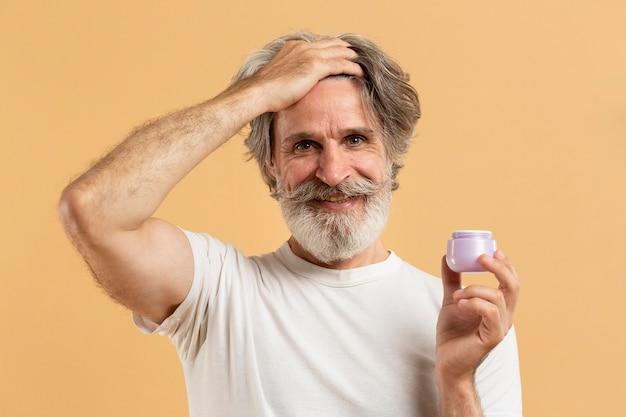 Vue de face de l'homme senior barbu tenant le gel capillaire