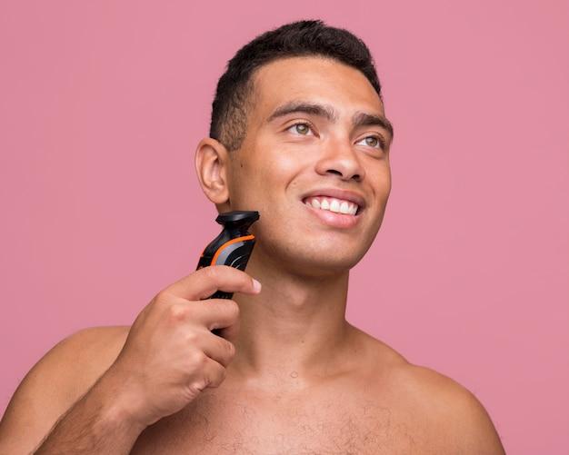 Vue de face de l'homme smiley torse nu à l'aide d'un rasoir électrique