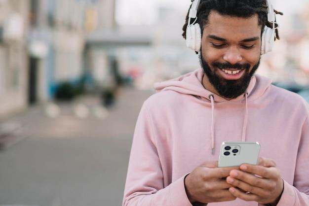 Vue de face de l'homme souriant à l'aide de smartphone avec un casque à l'extérieur
