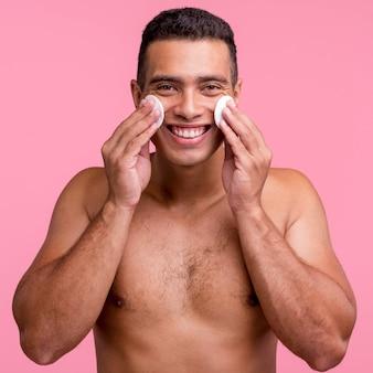 Vue de face de l'homme souriant à l'aide de tampons de coton sur son visage