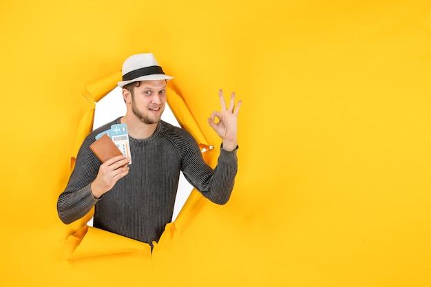 Vue de face d'un homme souriant avec un chapeau tenant un passeport étranger avec un billet et faisant un geste de lunettes dans un mur jaune déchiré