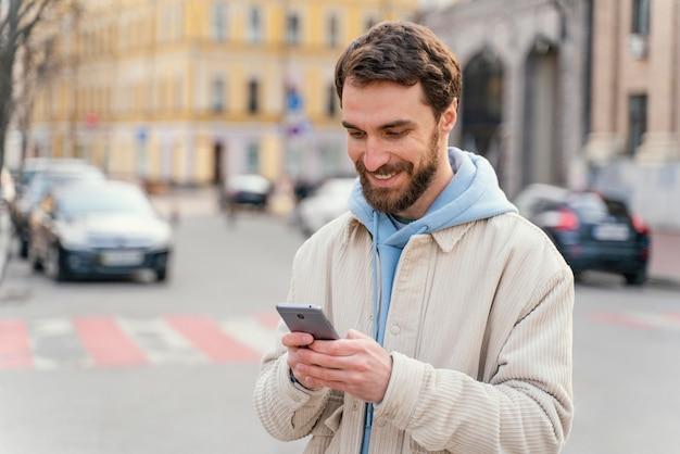 Vue de face de l'homme souriant à l'extérieur dans la ville à l'aide de smartphone