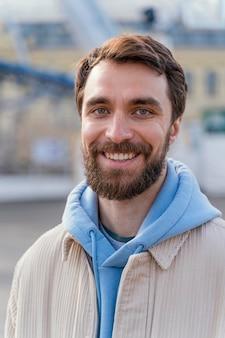 Vue de face de l'homme souriant à l'extérieur dans la ville