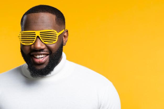 Vue de face homme souriant avec lunettes de soleil