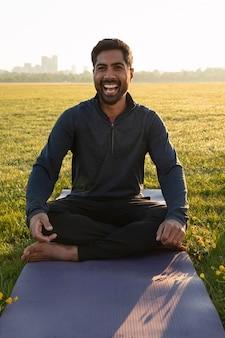 Vue de face d'un homme souriant méditant à l'extérieur sur un tapis de yoga