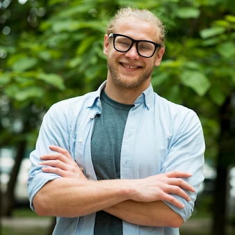 Vue de face de l'homme souriant posant à l'extérieur