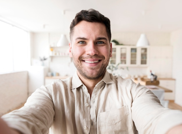 Vue de face homme souriant prenant selfie