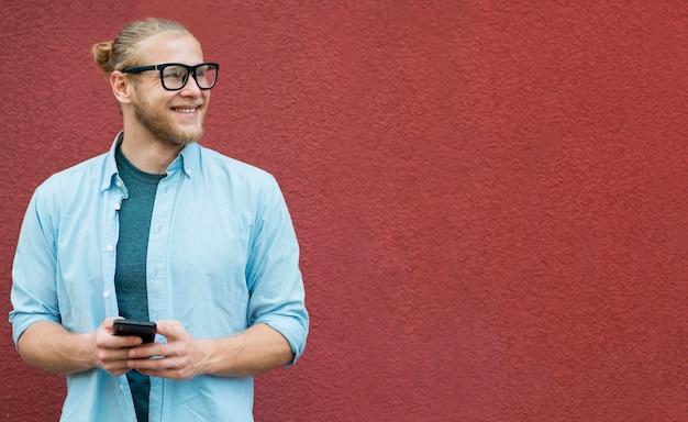 Vue de face de l'homme souriant tenant le smartphone
