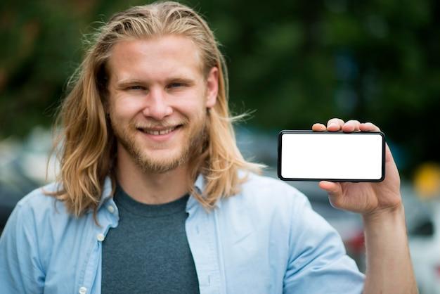 Vue de face de l'homme souriant tenant le téléphone