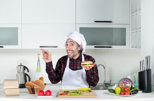 Vue de face homme surpris brandissant un hamburger debout derrière la table de la cuisine
