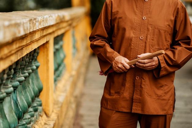 Vue de face de l'homme tenant de l'encens au temple