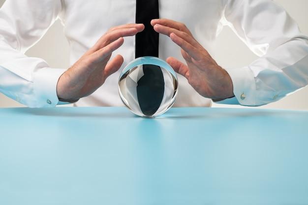 Vue de face d'un homme tenant des mains protectrices sur une sphère de cristal dans une image conceptuelle.