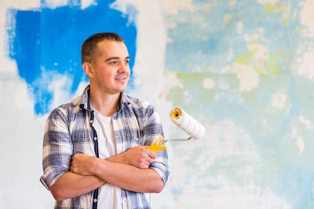 Vue de face d'un homme tenant un rouleau à peinture