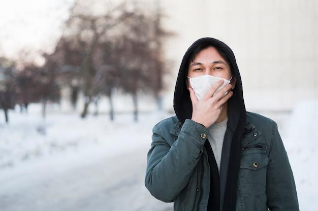 Vue de face de l'homme tenant son masque médical sur le visage tout en étant à l'extérieur