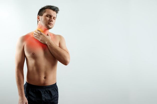 Vue de face, un homme tient ses mains derrière sa gorge