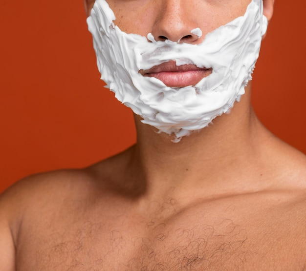 Vue de face de l'homme torse nu avec de la crème à raser sur son visage