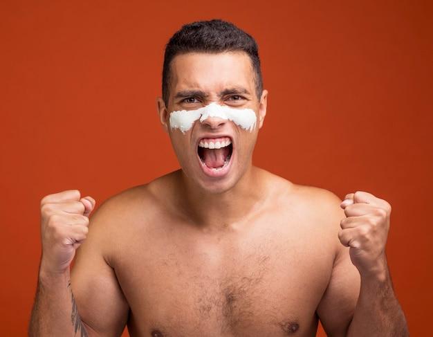 Vue de face de l'homme torse nu crier avec masque facial sur