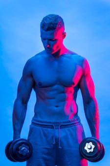 Vue de face de l'homme torse nu fit avec des poids