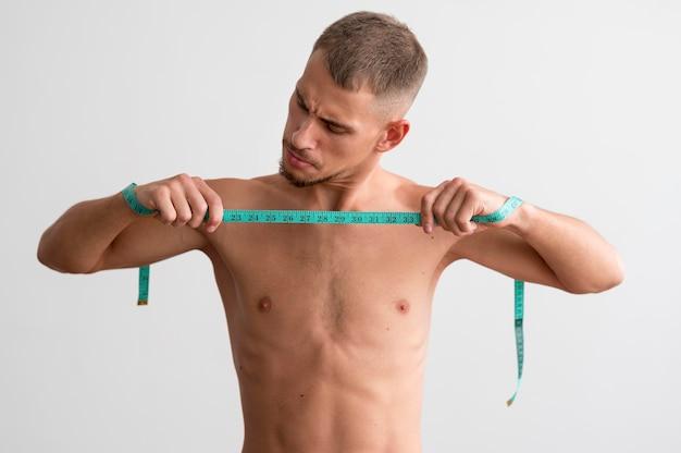 Vue de face de l'homme torse nu tenant un ruban à mesurer