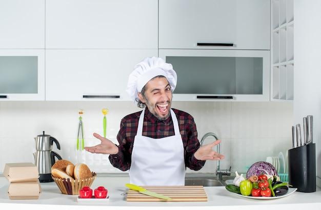Vue de face d'un homme très excité qui cligne des yeux, debout derrière la table de la cuisine dans la cuisine