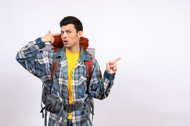Vue de face homme voyageur confus avec sac à dos mettant le pistolet à doigt à sa tempe