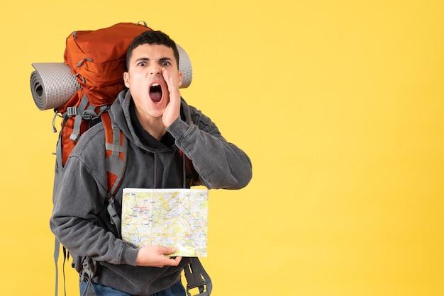 Vue de face homme voyageur hurlant avec sac à dos tenant la carte
