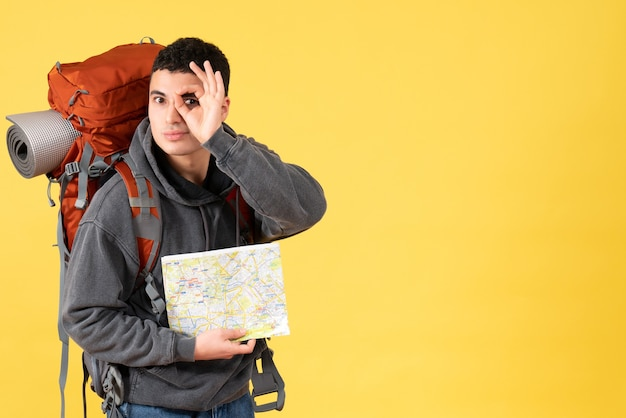 Vue de face homme voyageur avec sac à dos tenant la carte tenant un signe correct devant ses yeux