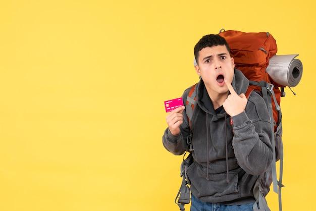 Vue de face homme voyageur surpris avec sac à dos rouge tenant une carte de crédit