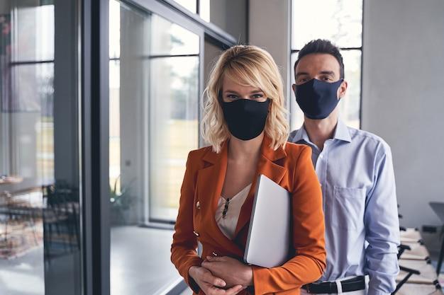 Vue de face d'hommes d'affaires portant des masques de protection au bureau pendant la période de quarantaine