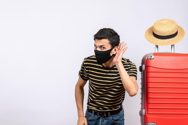 Vue de face indiscrets jeune touriste avec masque noir debout près de valise rouge écouter quelque chose