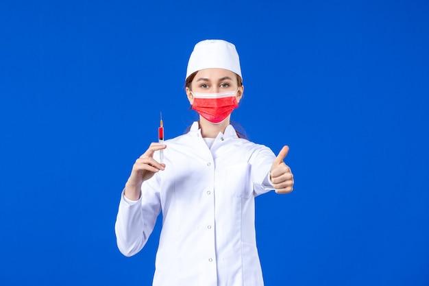 Vue de face infirmière en costume médical blanc avec masque rouge et injection dans ses mains sur bleu
